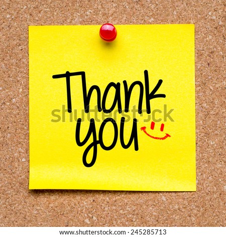 Note with Thank you. Blank yellow sticky note with Thank you sign and smile pined on a cork bulletin board. - stock photo