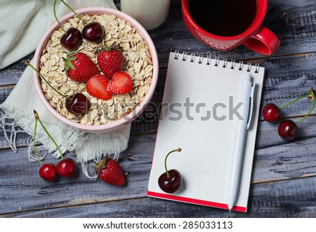 Notebook and breakfast with oat flakes, berry, milk. Selective focus - stock photo