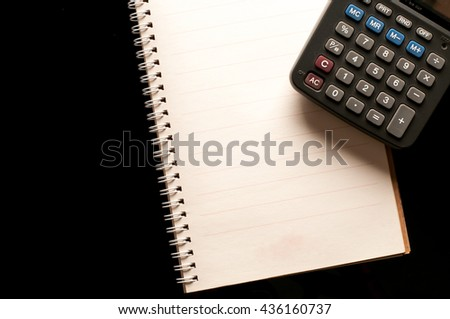 Notebook and calculator use in business office black background - stock photo