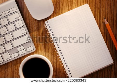 Notebook and Cup of Coffee near Computer Keyboard on Desk as seen from Above - stock photo