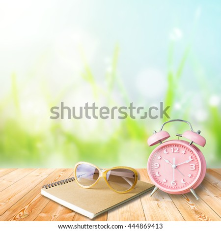Notebook and Glasses on Wood plank on natural green grass field,Spring or summer abstract nature blur background with grass in the meadow and blue sky in the back - stock photo