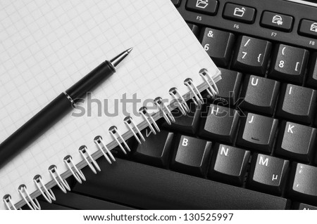 Notebook and pen on the black keyboard. Close up. - stock photo