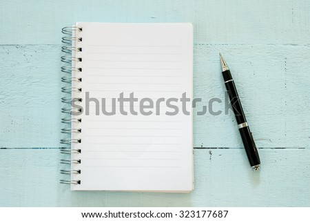 Notebook and pen on wooden table - stock photo