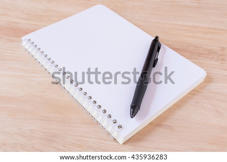 Notebook and pen placed on a wooden table in the office. - stock photo