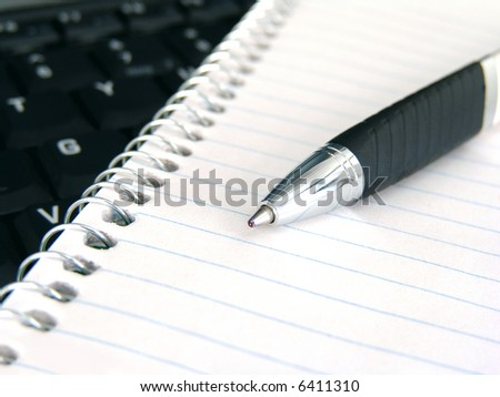 notebook and pen with keyboard in background - stock photo