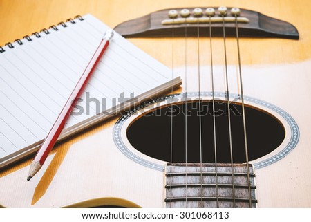 Notebook and pencil with guitar for writing music , Concept of music  - stock photo
