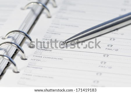 Notebook and silver pen,focus is set on the ballpoint pen - stock photo