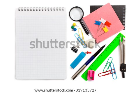 Notebook and stationery items beside on white background - stock photo