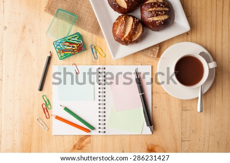Notebook and sticky paper, paper clip, color pencil, and pen on wood table in vintage style - stock photo