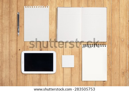 Notebook and tablet on wood table for background - stock photo