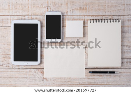 Notebook and tablet on wood table for text and background - stock photo