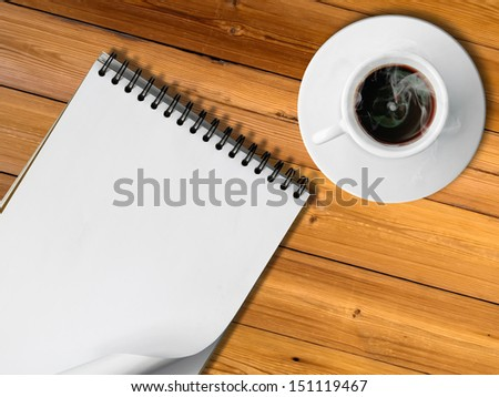 Notebook and White cup of hot coffee on wood table - stock photo