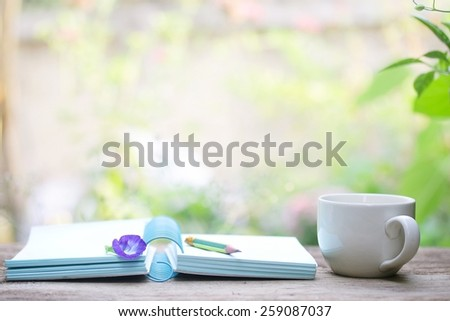Notebook  and  white cup on wooden table - stock photo