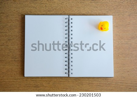 notebook and yellow duck on wood desk - stock photo