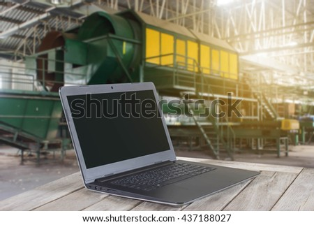 Notebook computer on a wooden table with blur Old factory garbage background - stock photo