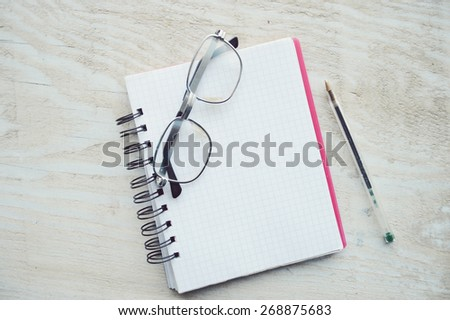 notebook, diary, glasses, pen, magnifying loupe close-up on a wooden table - stock photo