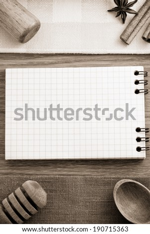 notebook for cooking recipes on wooden table - stock photo