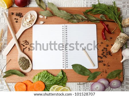 notebook for recipes and spices on wooden board - stock photo