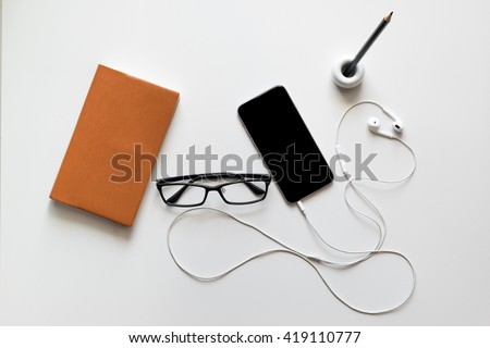 Notebook, glasses, smart phone, ear phone and pencil on white desk background - stock photo