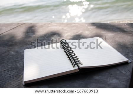 Notebook on desk and sea background. - stock photo