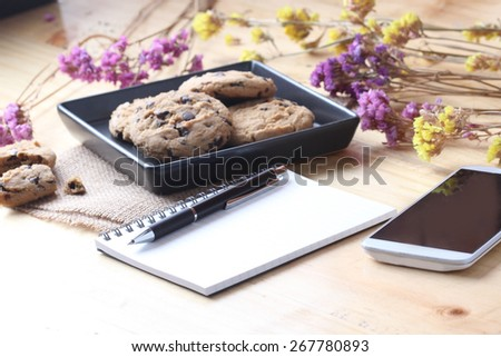 notebook on desk with coffee biscuit and pen,Office concept - stock photo