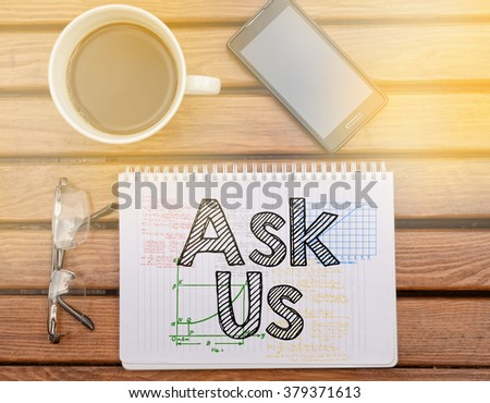 Notebook on table with text inside: Ask Us - stock photo