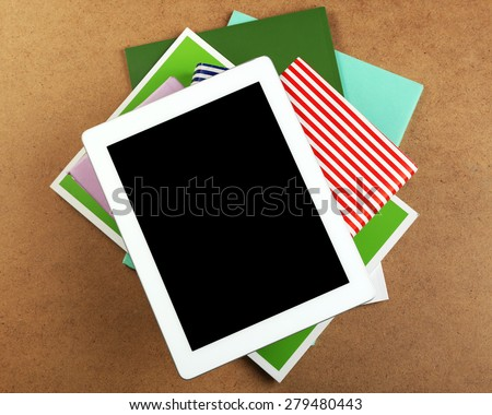 Notebook on top of pile of books and magazines on wooden background - stock photo