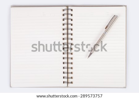 notebook open blank page with line and date text in the corner on white background, that has black spiral ring binder, and a silver pen put on the right page - stock photo
