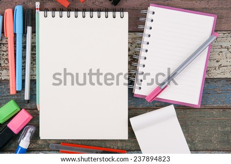 Notebook paper and school or office tools on vintage wood table background - stock photo