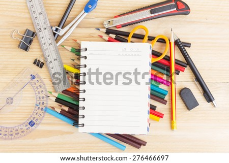 Notebook paper and school or office tools on wood table for background-vintage effect - stock photo