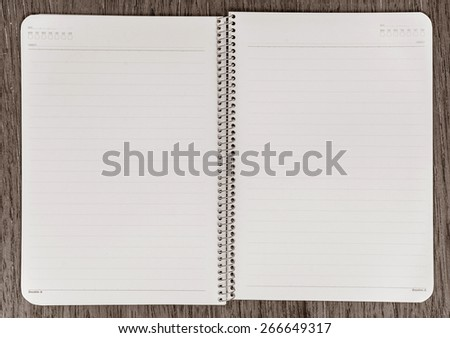 Notebook paper with on wooden background. - stock photo