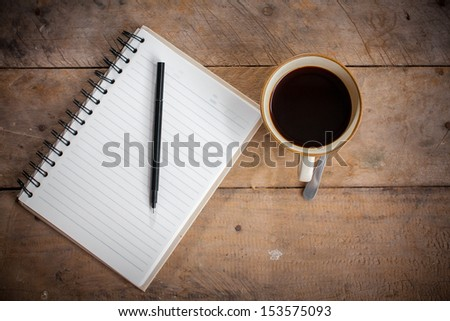 notebook pen and cup of coffee in wood table - stock photo