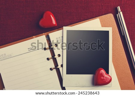 Notebook, photo and hearts on fabric background - stock photo