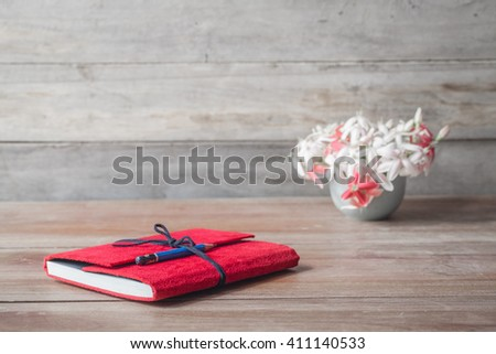 Notebook red flower vase on the old wooden floor. - stock photo