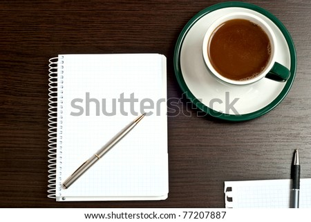 Notebook, silver pen and cup of coffee on dark desk - stock photo