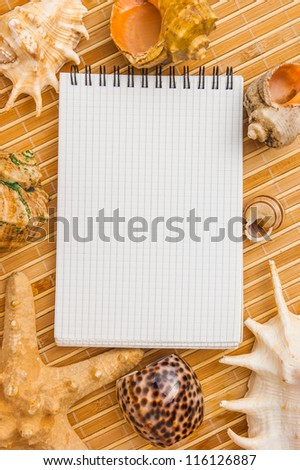 notebook to record notes on a background of seashells and starfish - stock photo