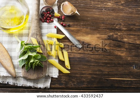 Notebook to write recipes for cooking on a dark wooden background with sprig of fresh aromatic oregano on a wooden blade. Selective focus. Horizontal - stock photo