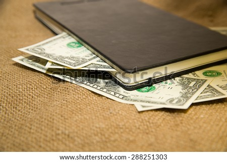 notebook with a blank sheet and money on the old tissue - stock photo