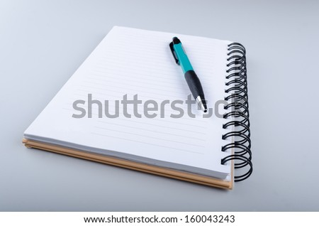 Notebook with a pen on top of it - stock photo