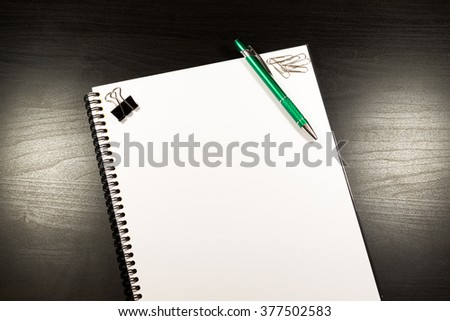 Notebook with Blank sheet of paper and Pen on wooden table background. Writing Idea concept or business concept - stock photo