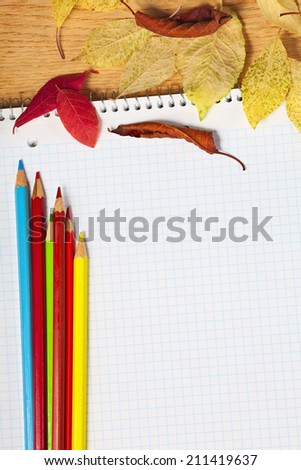 Notebook with colored pencils and autumn leaves on a wooden surface. - stock photo