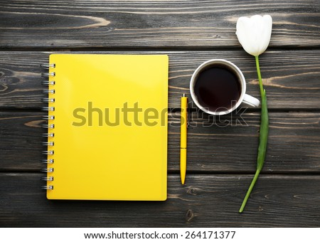 Notebook with cup of coffee and white tulip on wooden background - stock photo