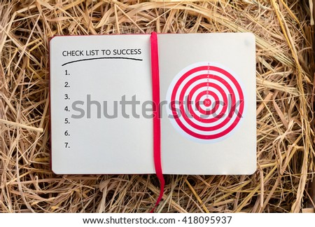 notebook with dart and check list to success business concept - stock photo