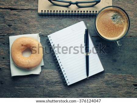 Notebook  with Donut and  Black coffee on wooden table -Vintage effect style. - stock photo