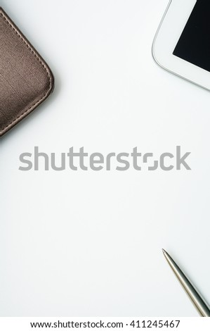 Notebook with leather cover, silver ballpoint pen and computer tablet on white background.Copy space in the center from top view - stock photo
