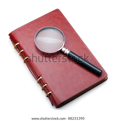 Notebook with magnifying glass on white isolate - stock photo