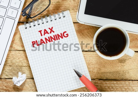 Notebook with tax planning. Workplace with keyboard , tablet pc , coffee, notebook with tax planning and pen on wood table - stock photo