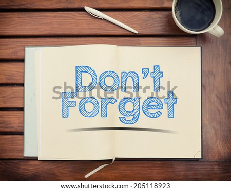 Notebook with text Don't Forget inside on table with coffee - stock photo