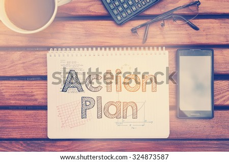 Notebook with text inside Action Plan on table with coffee, mobile phone and glasses.  - stock photo