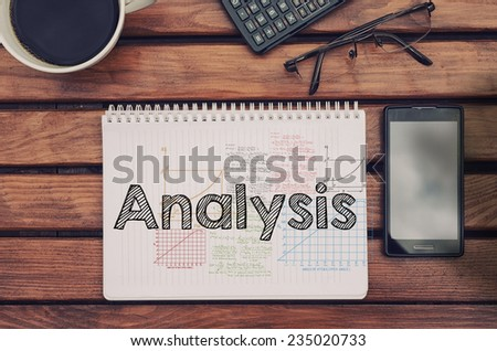 Notebook with text inside Analysis on table with coffee, mobile phone and glasses.  - stock photo
